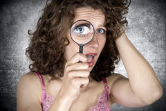 Look. Beautiful woman looking through a magnifying glass Royalty Free Stock Photography