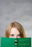 Look behind the book. Girl hiding behind the book, staring at you Stock Photos