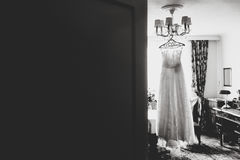 A look from behind a door on a white dress hanging on the chande Stock Photo
