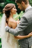 Look from behind at stylish wedding couple standing in calm gard Stock Photo