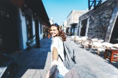 Look from behind at young woman holding man`s hand in `Follow me. ` pose, young cute female traveler with backpack royalty free stock image