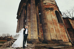 A look from below on the stunning wedding couple posing behind a. Ruined cathedral Royalty Free Stock Photos