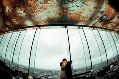 A look from below on a wedding couple standing in the panoramic. Restaurant in a gray clouded weather Stock Photos