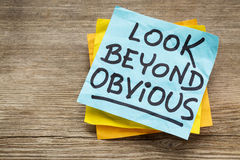 Look beyond obvious note. Look beyond obvious - creativity and motivation reminder on a sticky note against grained wood Stock Photography