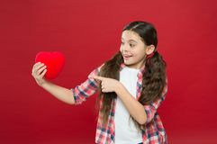 Look at this big heart. Cute girl in love. Having heart problem and heartache. Happy valentines day. Little girl. Pointing finger at red heart. Little child stock photo