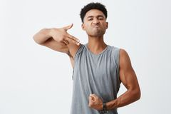 Look at this body. Portrait of young dark-skinned serious man with afro hairstyle showing gun gesture with hand royalty free stock image
