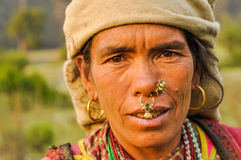 Look of brown eyes in Nepal. Dolpo, Nepal - circa May 2012: Native woman with brown headcloth has large earrings and piercings in her nose with brown eyes in Royalty Free Stock Images