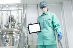 Industrial scientist shows tablet. Look at camera, white tablet, scientist shows tablet royalty free stock images