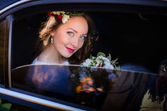 Look through the car`s window at wonderful bride sitting inside Stock Image