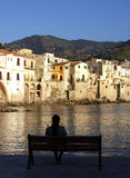 Look cefalu. Old town Cefalù in Sicily at summer with woman on the bench Royalty Free Stock Photography