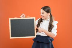 Look at this. cheerful school girl with blackboard. happy pupil in school uniform. copy space. commercial marketing. Conept. business school advert. new royalty free stock photography