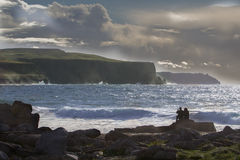 Look at the cliffs. Couple on rocks looking over sea at the Cliffs of Moher, Ireland Royalty Free Stock Photo