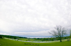 Look at those Clouds!. A landscape with a large leafless tree and pastures separate by white board fences taken before a storm. taken with a fish-eye lens to Royalty Free Stock Image