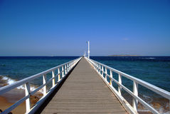 Look down the pier. A view to the ocean from a pier with the pier stretching into the distance Royalty Free Stock Image