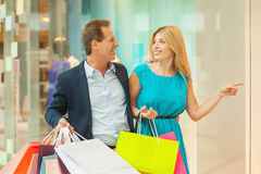 Look at this dress!. Beautiful mature couple shopping together while women pointing away and smiling Stock Photos