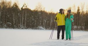 Look at each other with loving eyes while skiing in the winter forest. a married couple practices a healthy lifestyle stock video footage