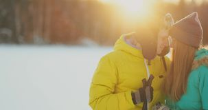 Look at each other with loving eyes while skiing in the winter forest. a married couple practices a healthy lifestyle stock video