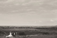 A look from far on the wedding couple walking on the field Stock Photography