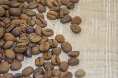 Fried coffee beans on a wooden base. A look at the fragrant, roasted coffee in a grain on a wooden surface Stock Photo