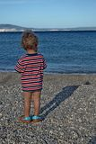 Look in the future. Baby boy looking in front on a pebble beach shore Stock Photography