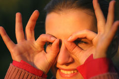 Look into the future. A woman imitating a look through glasses. focus on the eye Stock Photos
