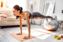 Serious international sportswoman doing fitness at home stock photos