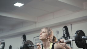 Look of girl holding a barbell with weights on her shoulders when she squats 4K stock video footage
