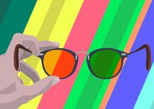 Look through glasses. Somebody`s hand holding glasses so you like looking through them on abstract multicolored background Royalty Free Stock Images