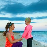 Mother and daughter on seacoast in evening having fun time Stock Photo