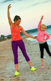 Healthy mother and daughter on beach in evening stretching Royalty Free Stock Images