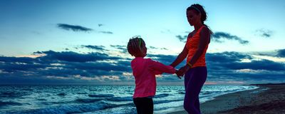 Mother and daughter on seacoast on sunset having fun time Stock Image