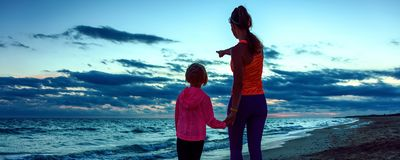 Mother and child on seashore on sunset pointing at something Royalty Free Stock Photography