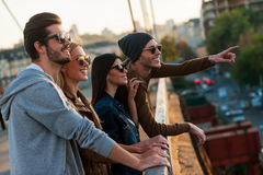 Look at that!. Group of young people standing close to each other on the bridge while one cheerful men pointing away Royalty Free Stock Photo