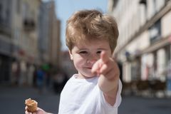 Look at that haircut. Small child point finger on street. Little boy with stylish haircut. Little child with short blond. Hair. Hair care products. Healthy hair stock photography