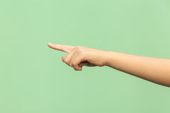 Look this! Hand finger pointing isolated on green background. Studio shot Royalty Free Stock Photography