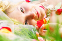 A look of the happy bride. Lie on the grass and rose petal Royalty Free Stock Photo