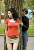 Look at her. Pretty woman and a man hiding behind a tree Stock Photos