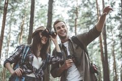 Positive young couple is traveling across forest stock photos