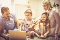 Look here. Family at home using laptop together royalty free stock photography