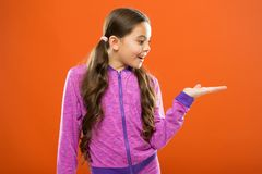Look here. Kid happy smiling face show something on open palm copy space. Girl demonstrate product. Advertisement and. Commercial concept. Promoting product for royalty free stock images