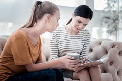 Skilled psychologist consulting a girl. Look here. Skilled psychologist showing her notes while the girl sitting on the sofa and expressing interest Stock Photography