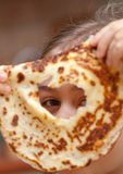 Look through the hole in pancake. Little girl looking through the hole in pancake. Funny breakfast Stock Photo