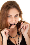 Look how my teeth are strong. Beautiful smiling woman with white teeth is biting a black necklake Stock Images
