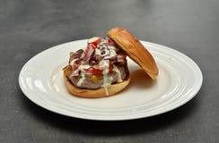 Look inside tasty hamburger on white plate Stock Photo