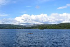 A look of the lake in UK. The photo is taken around the lake district in the UK. There are some boats, yachts on the blue lake. Green mountains encircle the lake stock images