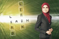 Look at Learn, lead and earn word box on her left over abstract background. Young woman standing, look at Learn, lead and earn word box on her left over abstract Royalty Free Stock Images