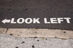 Look left. White lettering and arrow, warning sing, on asphalt road, at a pedestrian crossing. Street of Sydney, Australia royalty free stock photo