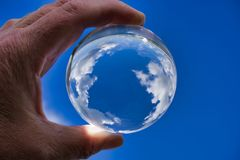 Lensball with Clouds. A look through a lensball at the clouds makes it look like earth royalty free stock photography
