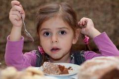 Look of little girl eating cake. Dessert Royalty Free Stock Images
