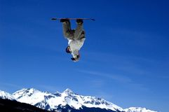 Look ma no land!. Snowboarder inverted in air suspended above distant snow covered peaks Royalty Free Stock Image